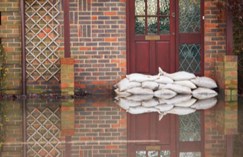 Sandbags in front of a red door on a flooded street